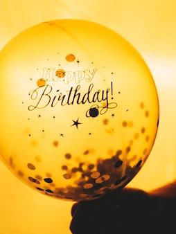 Hand holding Happy Birthday balloon