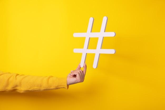 Рука, держащая символ хэштега, делает важную тему популярной, задает тенденции в интернете.