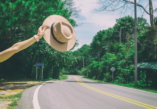 Hand holding a hat in the tourism travel hitchhiking