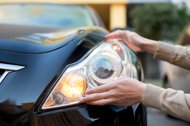 Hand holding headlight of dark car