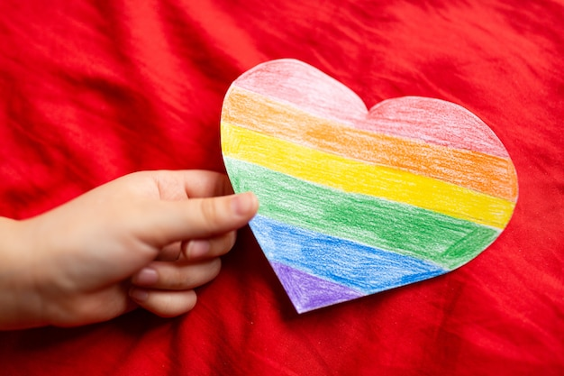 Hand holding heart coloured in lgbtq pride colours