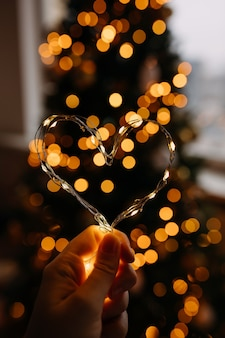 Hand holding heart made of fairy lights on blurry background.