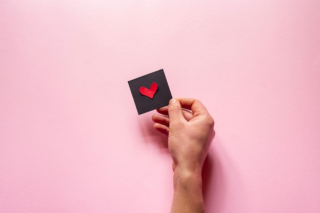 The hand  holding a heart  over pink wall, valentine's day. flat lay