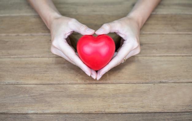 Hand holding heart shape on wood