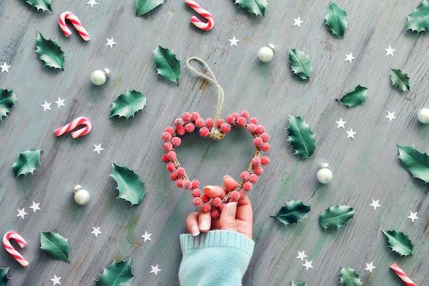 Рука держит сердечный венок, украшенный матовыми ягодами.