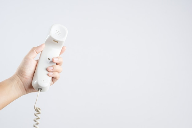 Hand holding home or office telephone with line