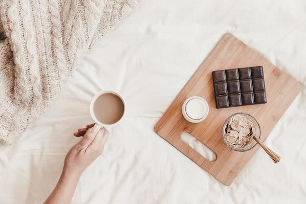 Handholding hot drinknear tastymeal on bedsheet