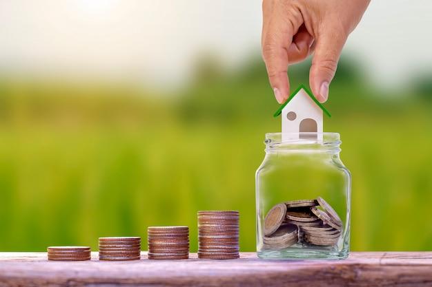 Рука держит модель дома в банке для экономии денег и стопки монет на деревянном полу