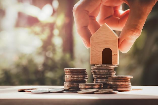 손을 잡고 집 모델 스택 동전, 구매 집, 재산, 모기지 및 부동산 투자에 대한 저축. 부동산 부동산 및 금융 개념입니다.