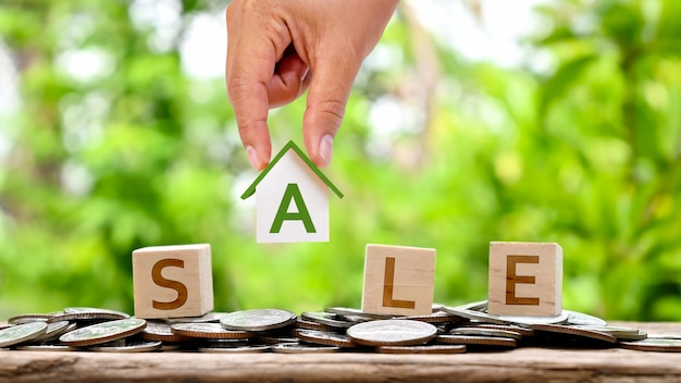 Hand holding house model and sale message on wooden blog home loan concept for real estate investment