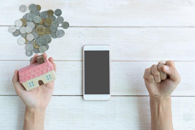 白い木製のテーブルで成功を祝う拳、住宅金融の概念、コピースペース、トップビューの貯蓄計画を上げながら家のモデルを持っている手