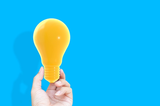Hand holding househand holding light bulb yellow pastel color on blue background