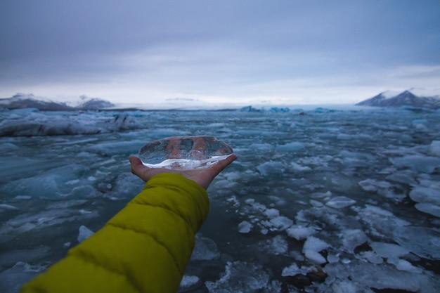 Mano che tiene il ghiaccio con un mare ghiacciato sotto un cielo nuvoloso in islanda sullo sfondo