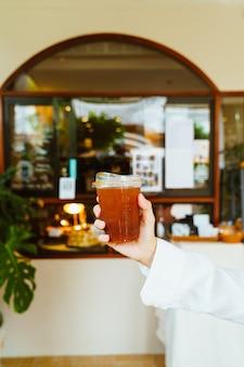 Рука держит холодный кофе американо в стакане на вынос