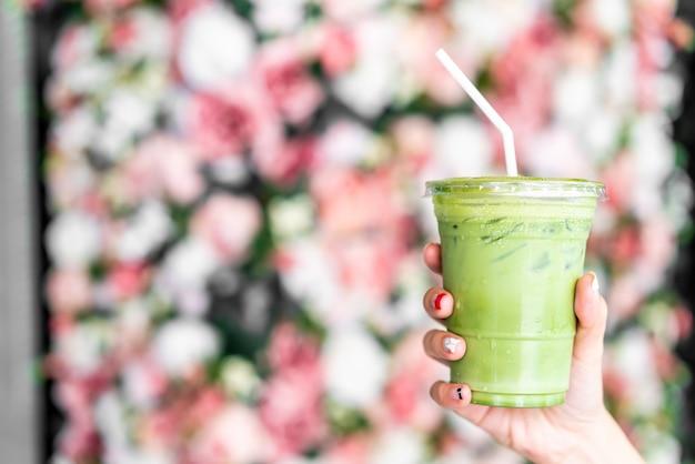 Hand holding iced matcha latte green tea cup