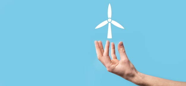 Hand holding an icon of a windmill that produces environmental energy on blue background.