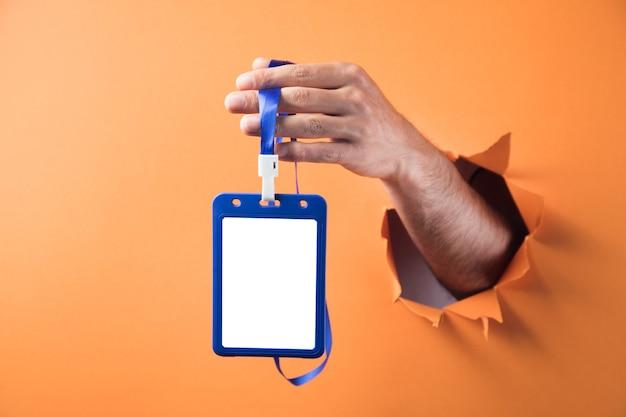Hand holding id tag on orange background