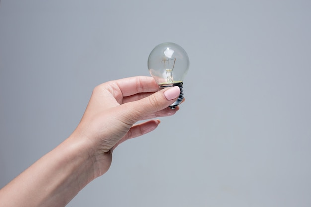 Hand holding an incandescent light bulb on gray space