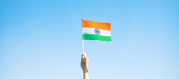 青空の背景にインドの旗を持っている手。インド共和国記念日の休日、幸せな独立記念日、ガンディー生誕記念日