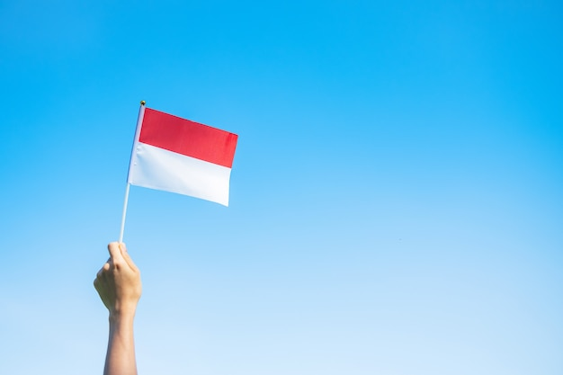 Hand holding indonesia flag on blue sky background. indonesia independence day, national holiday day and happy celebration concepts