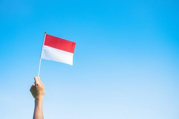 푸른 하늘 배경에 인도네시아 국기를 들고 있는 손. 인도네시아 독립 기념일, 국경일 및 행복한 축하 개념