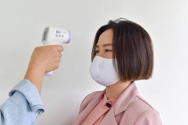 体温をチェックするために赤外線額温度計を持っている手。コロナウイルスからの保護の概念(covid-19)。