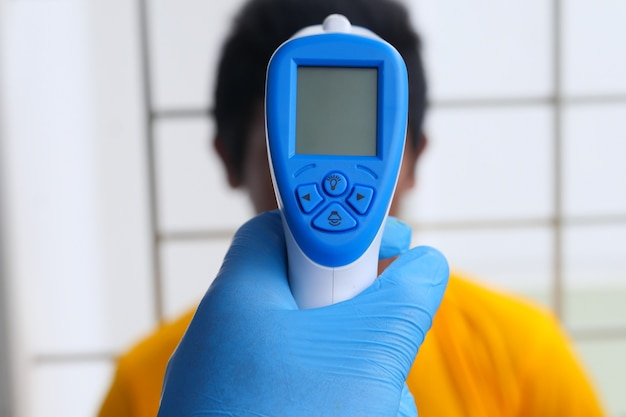 Hand holding infrared thermometer to measuring temperature.