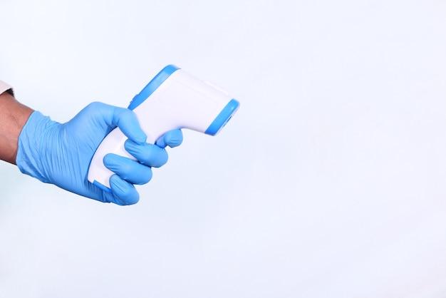 Рука, держащая инфракрасный термометр для измерения температуры, изолирована на белом