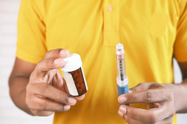 Рука, держащая инсулиновые ручки и контейнер для таблеток