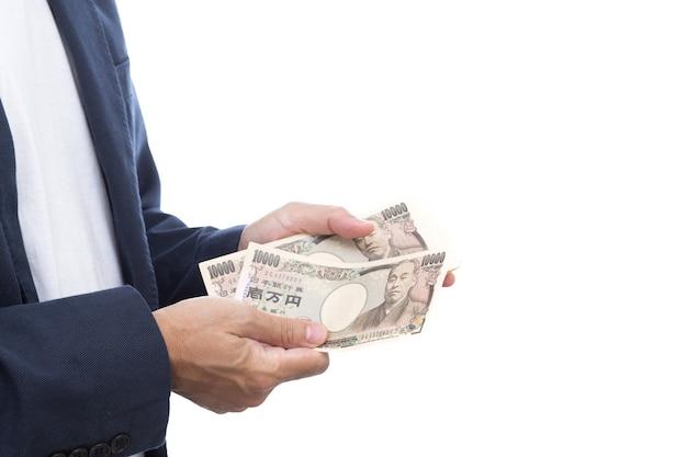 白い背景に日本の紙幣を持っている手。日本のお金。