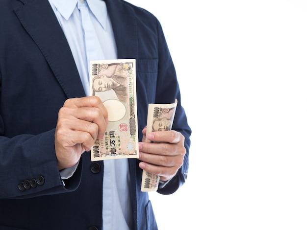 Hand holding japanese banknote on white background. japanese money.