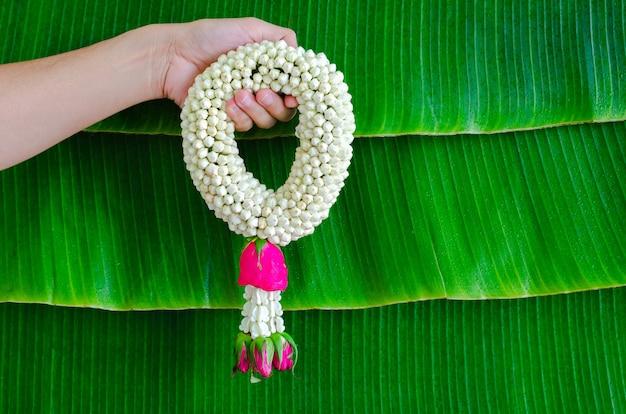 Hand holding jasmine garland with wet banana leaf background for songkran festival concept.