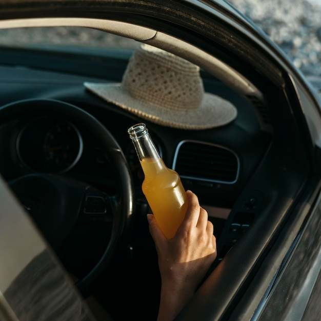 Hand holding juice bottle in car