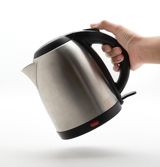 Hand holding the kettle at tilted angle like it's pouring water. silver electric kettle on a white background, water kettle, fast heating. modern technology brewing.