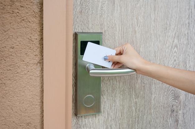 Рука, держащая сканирование ключ-карты, чтобы открыть деревянную дверь на курорте