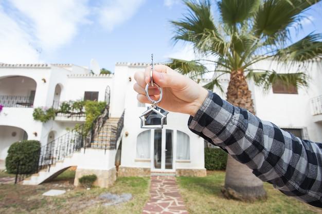 Рука держит ключ с брелком в форме дома.
