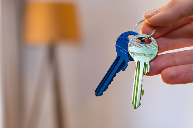 Hand holding keys with room on surface rent sell buy apartment real estate business