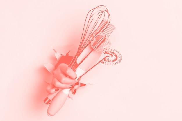 台所用品を持っている手。ベーキングツール-ブラシ、泡立て器、ヘラ。パン屋さん、料理、健康的な自家製食品のコンセプト