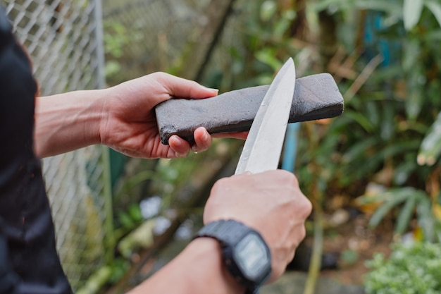 Hand holding knife and whetstone to shapen knife. manual sharpening knife.