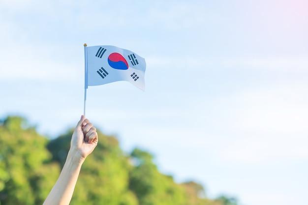 Hand holding korea flag on nature background. national foundation, gaecheonjeol, public nation holiday, national liberation day of korea and happy celebration concepts Premium Photo