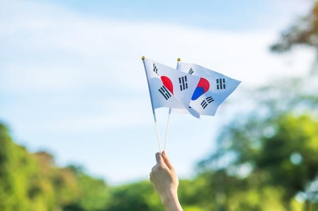 自然の背景に韓国の旗を持っている手。国立財団、開天節、国民の祝日、韓国の光復節、そして幸せなお祝いのコンセプト