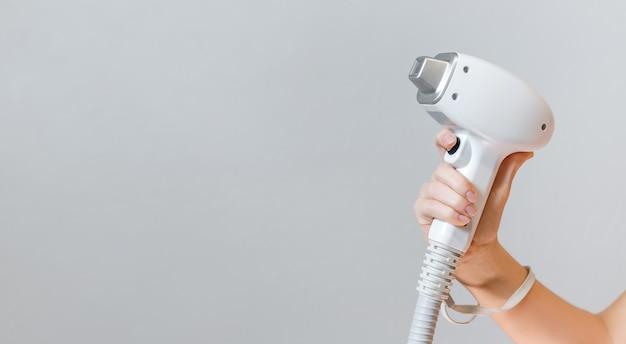 Hand holding laser hair removal machine on light grey machine