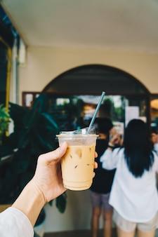 Hand holding latte coffee in takeaway glass
