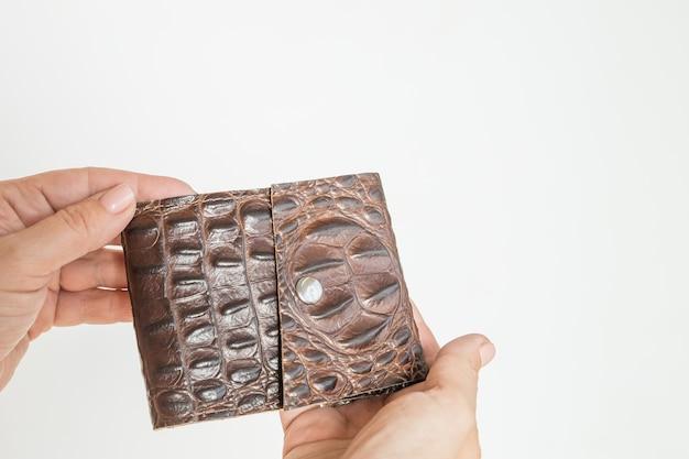 흰색 배경에 고립 된 가죽 갈색 지갑 지갑을 들고 손. 갈색 가죽으로 만든 남성용 액세서리로 돈과 카드를 위한 수제 지갑.손에 지갑