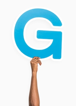 Hand holding the letter g