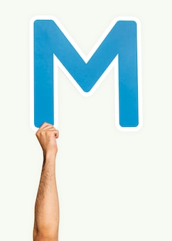 Hand holding the letter m