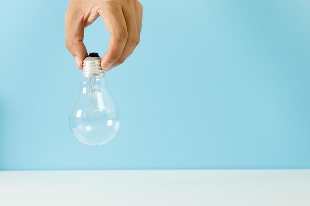 손을 잡고 전구 파란색 배경입니다. 창의성, 아이디어 및 창의적인 개념의 상징입니다.