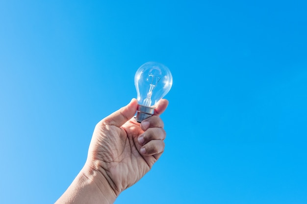 Hand holding light bulb and blue sky