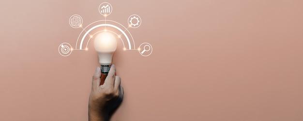 Рука, держащая лампочку на розовом фоне с иконами мозгового штурма и иконкой бизнес-источников, инновациями и креативной концепцией