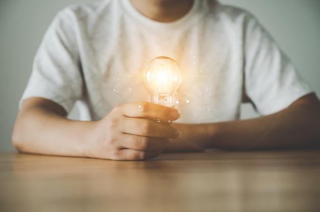 木製のテーブルに電球を持っている手。インスピレーションの概念創造的なアイデアの思考と将来の技術革新